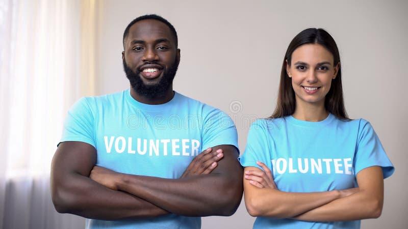 Volontaires de métis se tenant avec des mains croisées au centre de réhabilitation, aide images stock