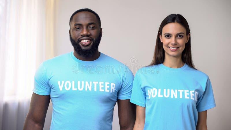 Volontaires multi-ethniques de sourire se tenant directement au centre de réhabilitation, aide image libre de droits