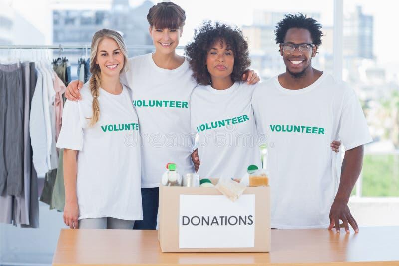 Volontaires se tenant devant la nourriture dans une boîte de donation image stock