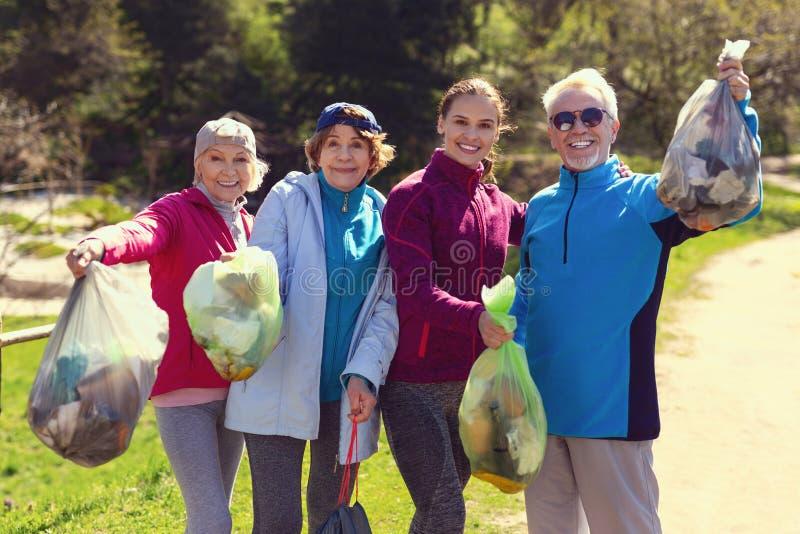 Volontari allegri che tengono i pacchetti con la lettiera fotografie stock