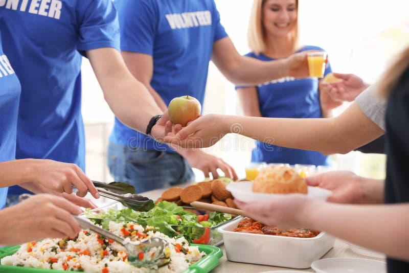 Volontari che serviscono alimento alla gente povera, fotografie stock