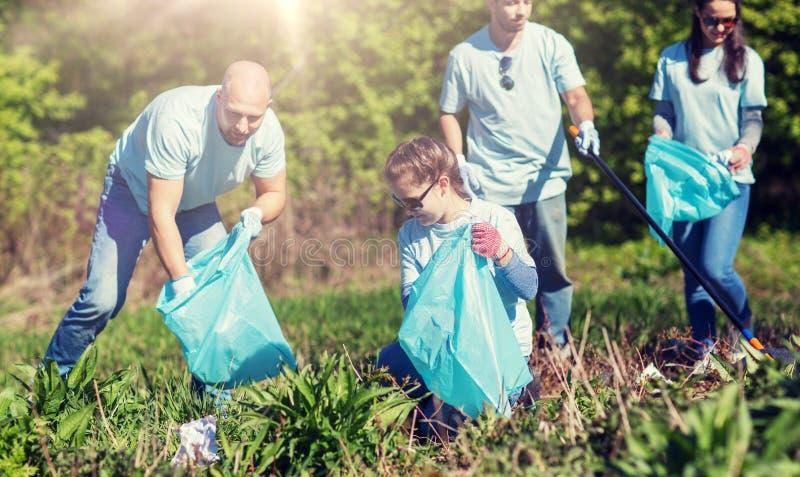 Volontari con le borse di immondizia che puliscono area del parco immagini stock
