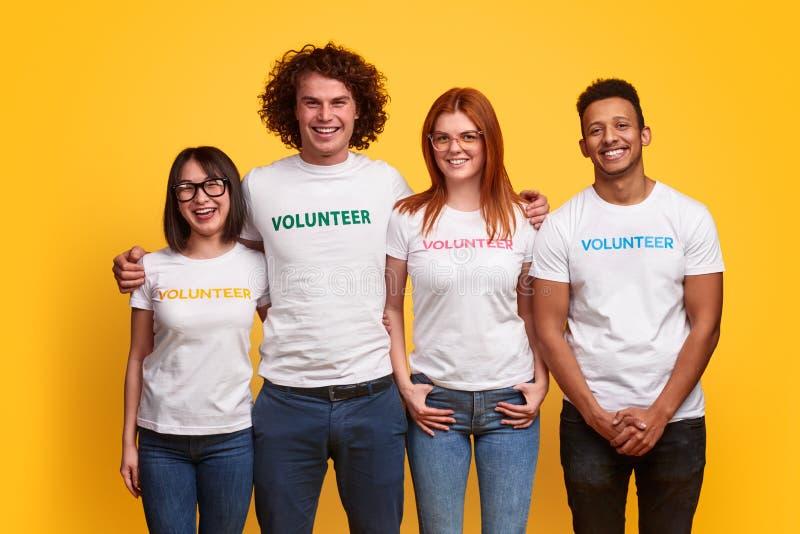 Volontari multietnici che sorridono per la macchina fotografica fotografia stock libera da diritti