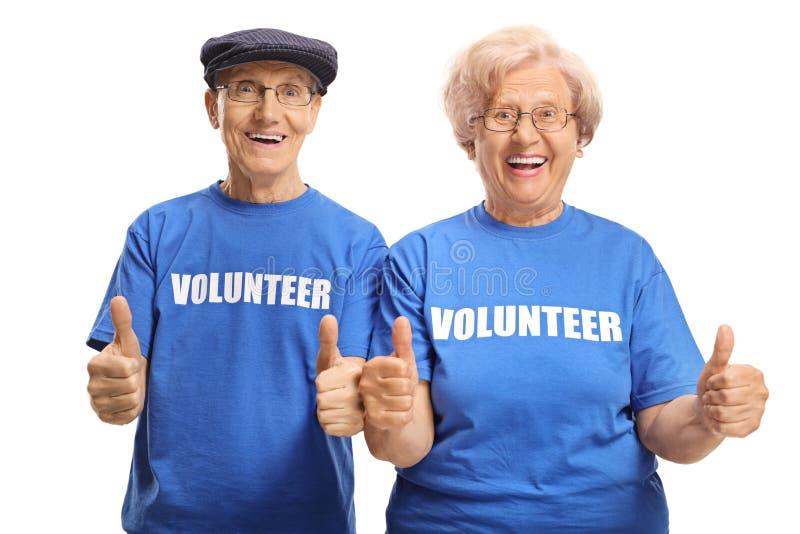 Volontari senior allegri delle coppie con i pollici su immagini stock