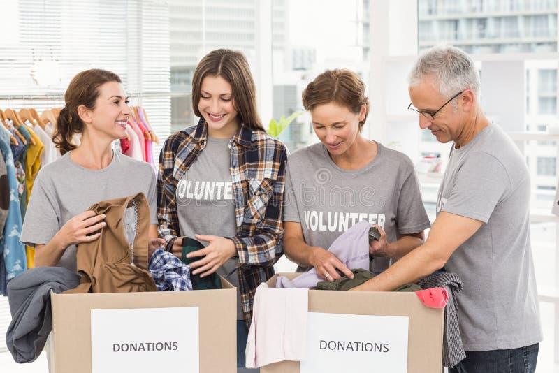 Volontari sorridenti che ordinano le scatole di donazione immagine stock