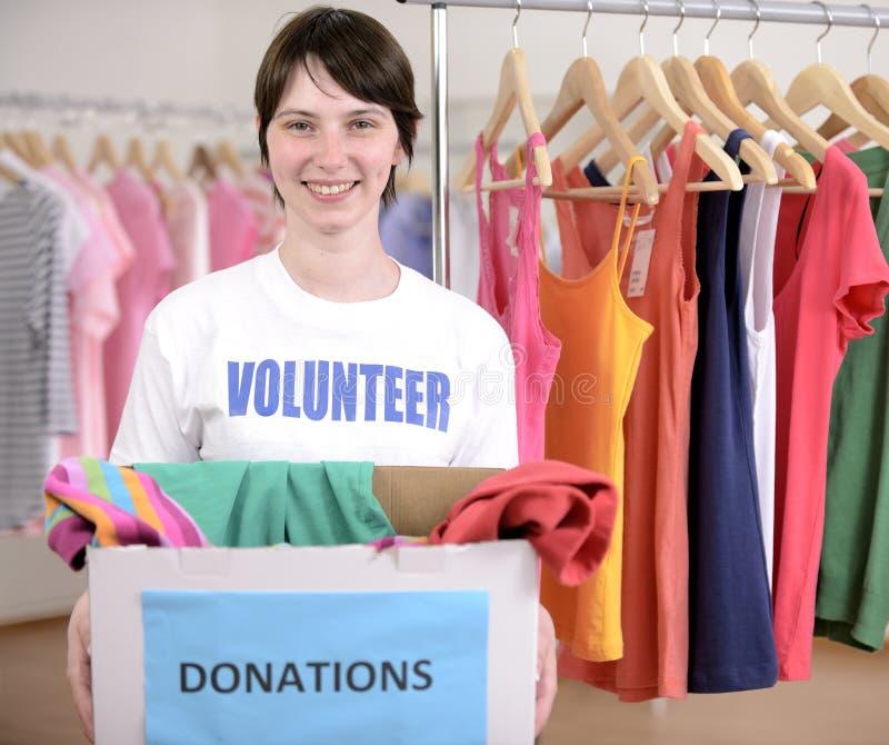 Volontario con la casella di donazione dei vestiti immagine stock