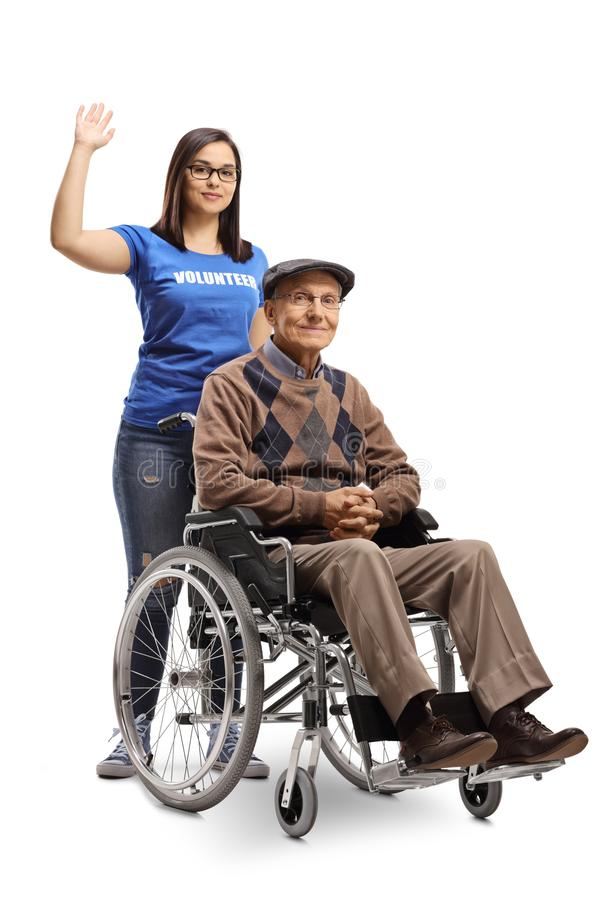 Volontario della giovane donna che spinge un uomo senior in una sedia a rotelle e che mostra i pollici su fotografia stock libera da diritti