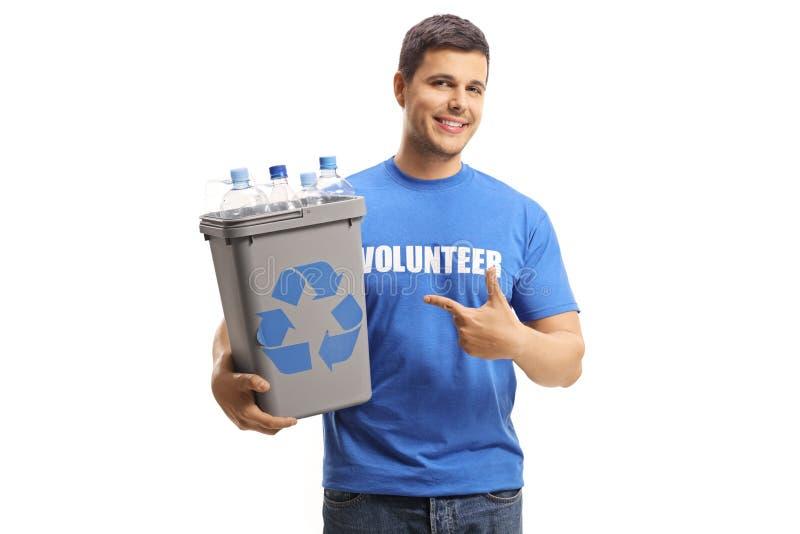 Volontario maschio sorridente che tiene indicare e le bottiglie con un recipiente di riciclaggio di plastica immagini stock