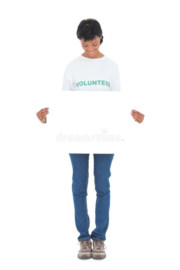Volontario moro divertente che tiene un pannello bianco davanti alla macchina fotografica fotografia stock libera da diritti