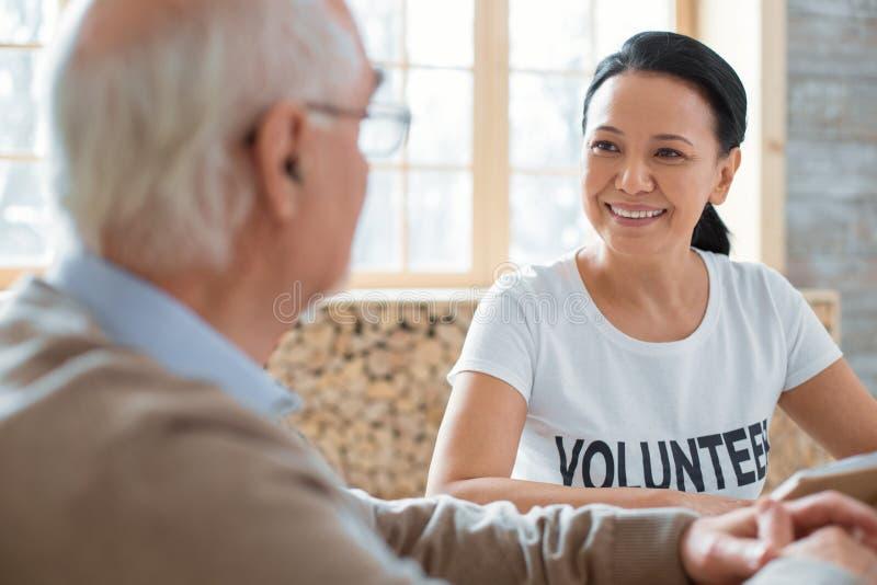 Volontario piacevole ed uomo senior che discutono libro immagine stock