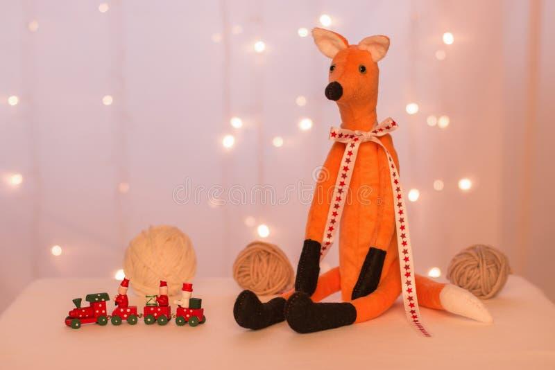 Volpe rossa fatta a mano che si siede sui precedenti delle luci di Natale, delle palle e di un treno di legno immagine stock libera da diritti