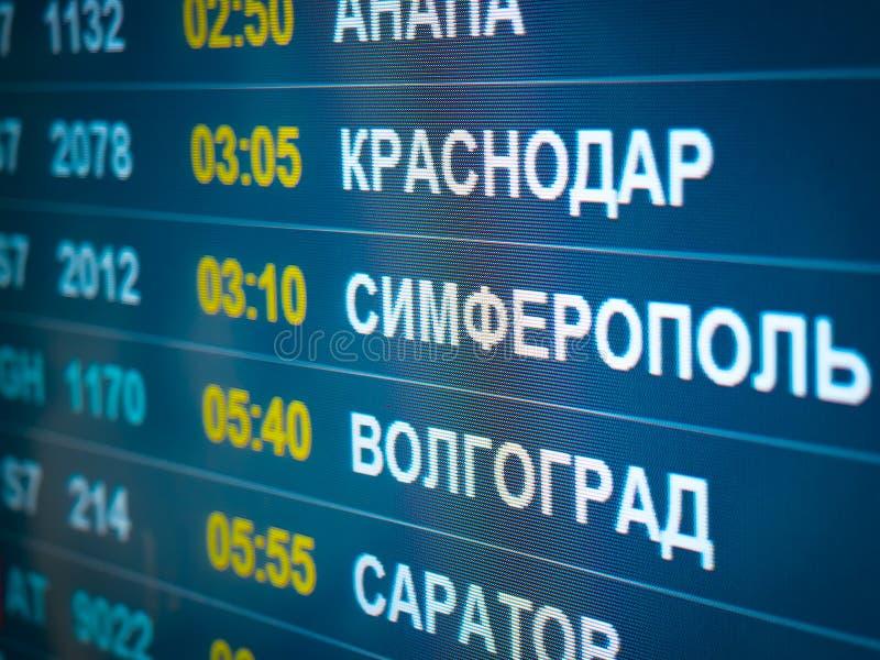 Vols et lignes aériennes électroniques de tableau indicateur Les destinations ont écrit dans la langue russe traduisent sont : Si photographie stock