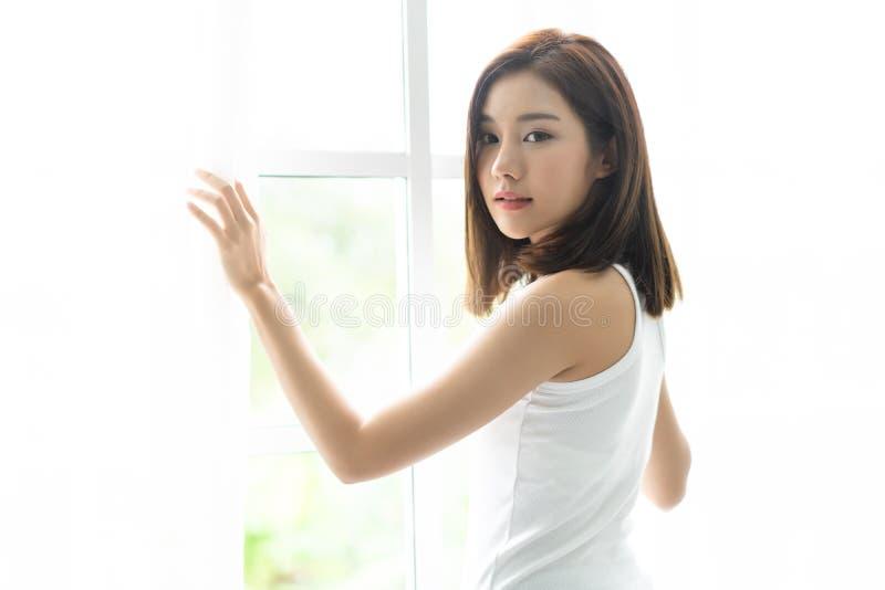Volta asiática alegre nova da mulher para trás e mantendo as cortinas abertas para olhar em casa fora da grande janela clara, gir imagens de stock royalty free
