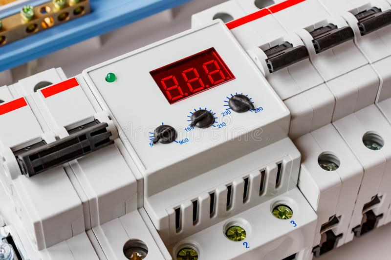Voltage limiter with automatic circuit breakers closeup in the white plastic mounting box closeup stock photos