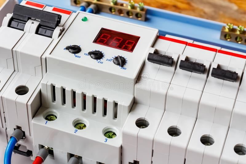 Voltage limiter and automatic circuit breakers closeup in the white plastic mounting box royalty free stock image