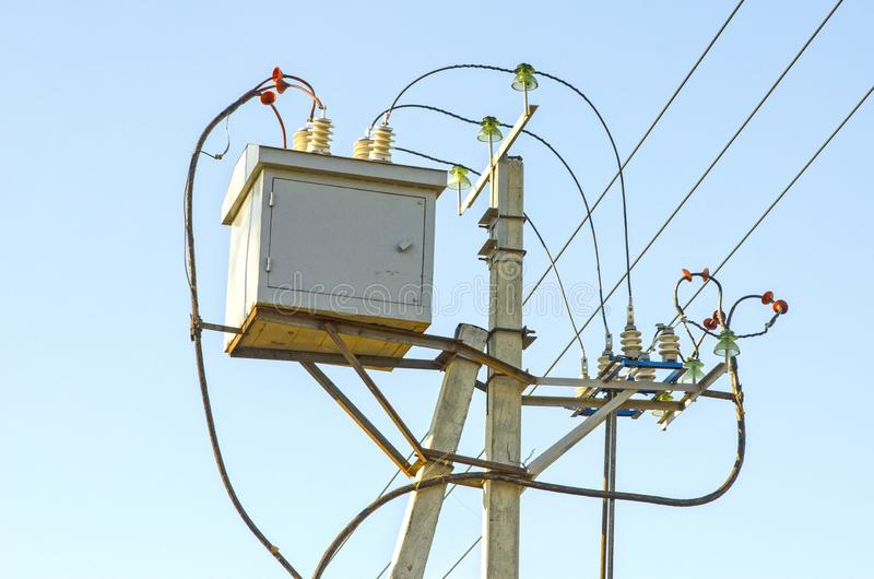 Voltage-reducing transformer is installed on the pole of the high-voltage transmission line support. Russia stock images