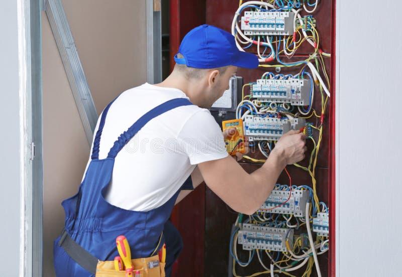 Voltaje de medición del electricista en tablero foto de archivo