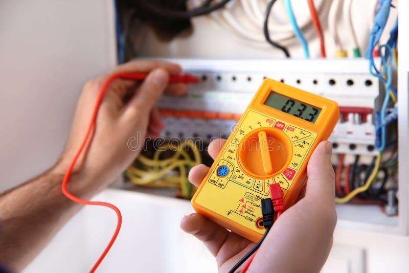 Voltaje de medición del electricista joven foto de archivo