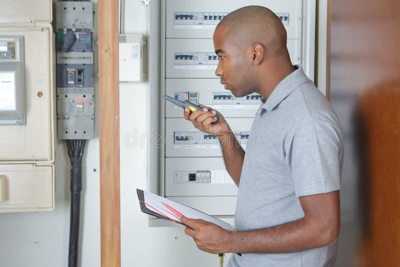 Voltaje de medición del electricista joven en tablero del fusible imagen de archivo libre de regalías