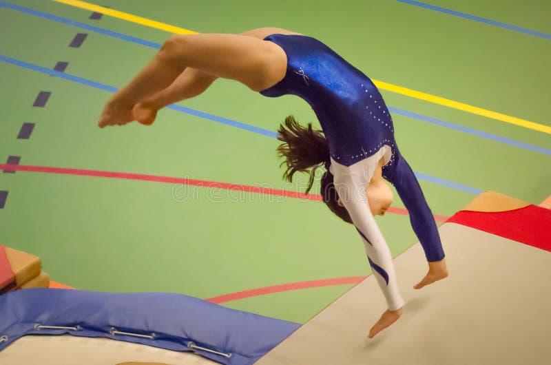 Voltereta sobre las manos de ejecución del salto de la muchacha joven del gimnasta detrás imagen de archivo
