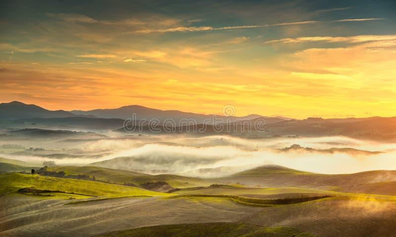 Volterra dimmig panorama, Rolling Hills och gräsplanfält på sunse arkivbild