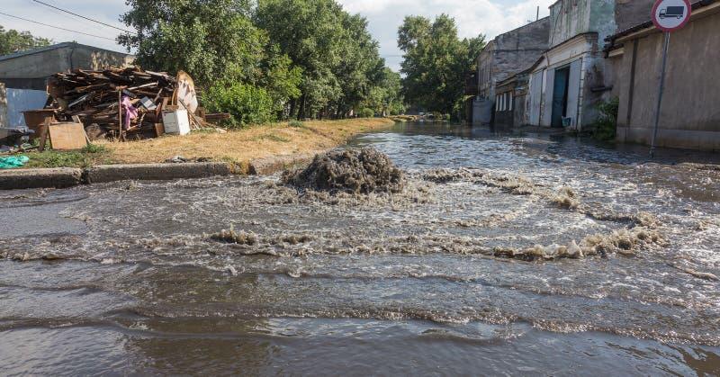 Volume de água fora do portal da água de esgoto da estrada Fonte da drenagem da água de esgoto Acidente do sistema de água de esg imagens de stock royalty free