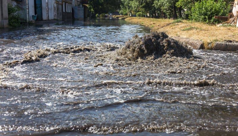 Volume de água fora do portal da água de esgoto da estrada Fonte da drenagem da água de esgoto Acidente do sistema de água de esg imagem de stock royalty free