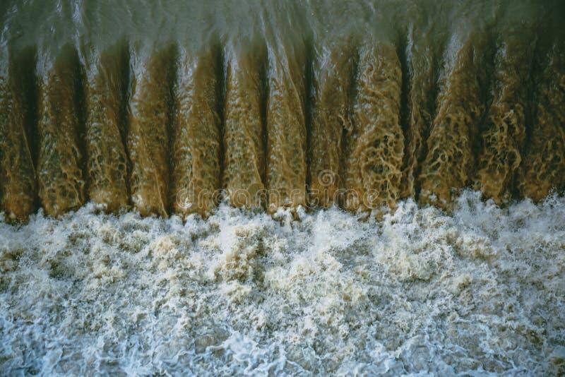 Volume de água poderoso na represa sintética perto da planta hidroelétrico foto de stock
