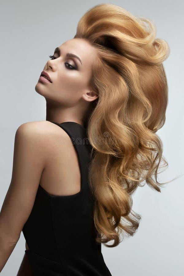 Volume dei capelli Ritratto di bella bionda con capelli ondulati lunghi fotografia stock