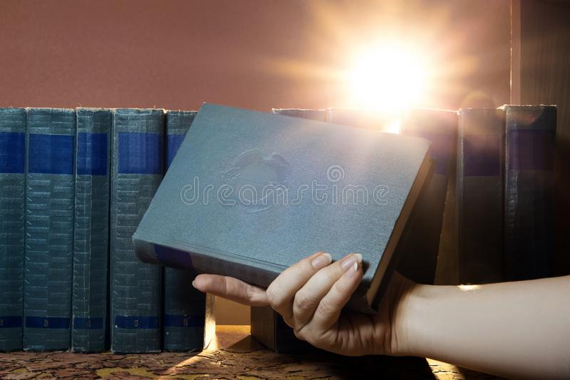 Female hand is holding a book, takes one book on the shelf. Light of knowledge. The pursuit of knowledge royalty free stock image