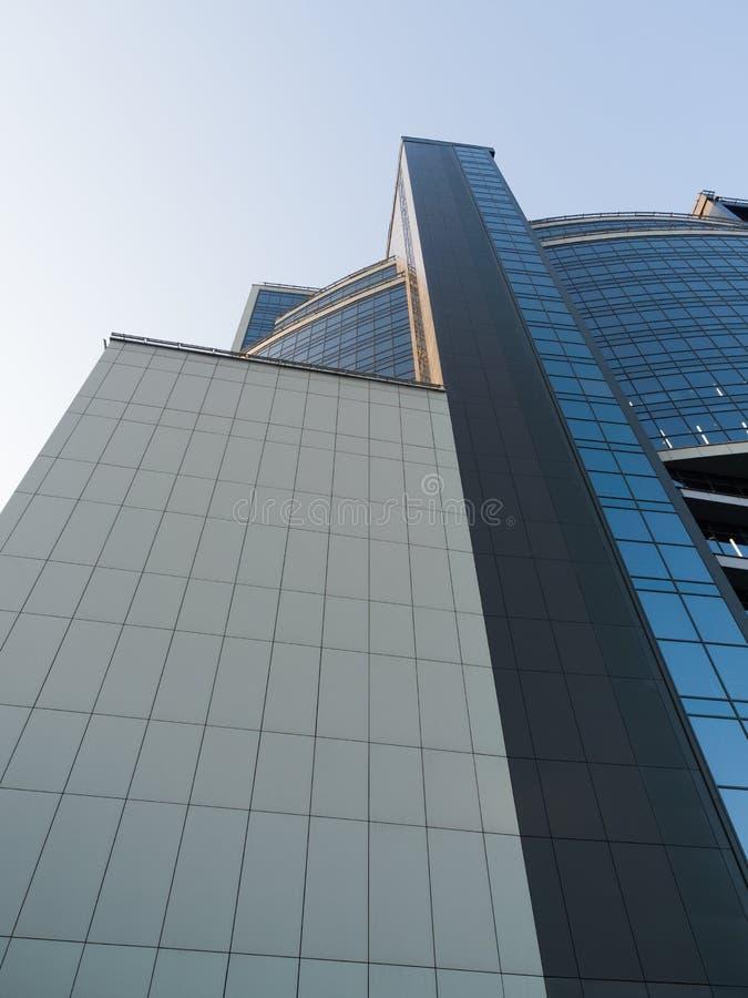 Volumes géométriques d'un nouvel immeuble d'affaires moderne face au ciel images stock