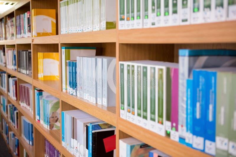 Volumes van boeken op boekenrek in bibliotheek royalty-vrije stock afbeelding
