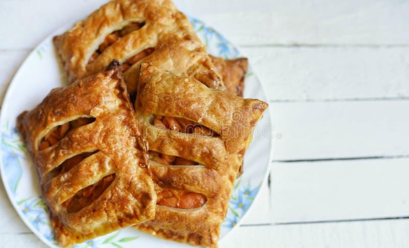Volumi d'affari della pasticceria della mela della pasta sfoglia per il dessert su una tavola di legno bianca con lo spazio della fotografia stock