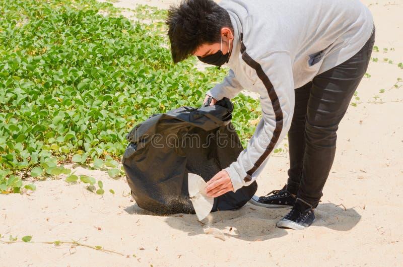 Voluntário da criança que recolhe o lixo na praia bonita na praia de Karon fotografia de stock