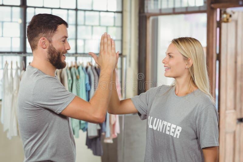 Voluntário de sorriso que faz a elevação cinco no escritório foto de stock royalty free