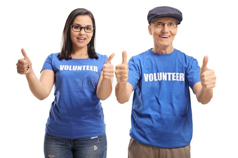 Voluntário fêmea novo e um voluntário masculino superior que mostra os polegares acima fotografia de stock