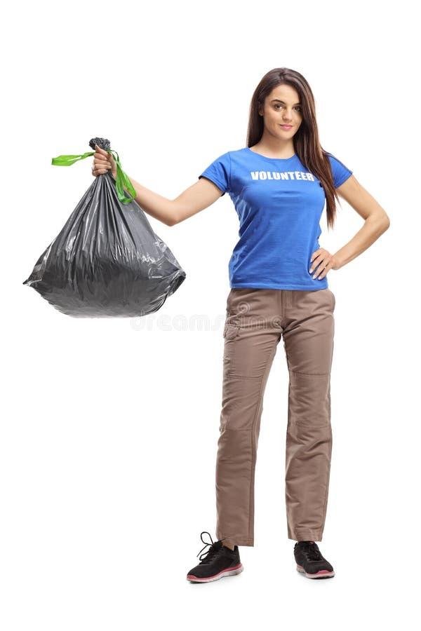 Voluntário fêmea novo que guarda um saco plástico do desperdício fotografia de stock