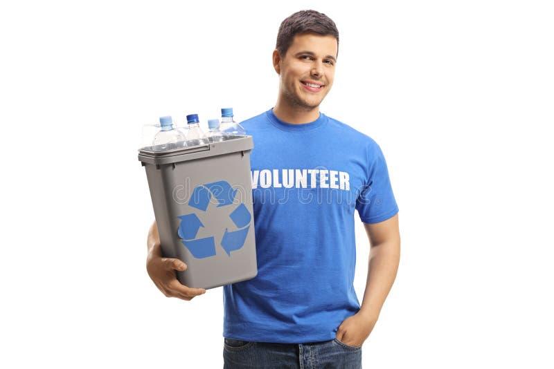 Voluntário masculino de sorriso que guarda um escaninho de reciclagem plástico com garrafas e levantamento imagens de stock royalty free