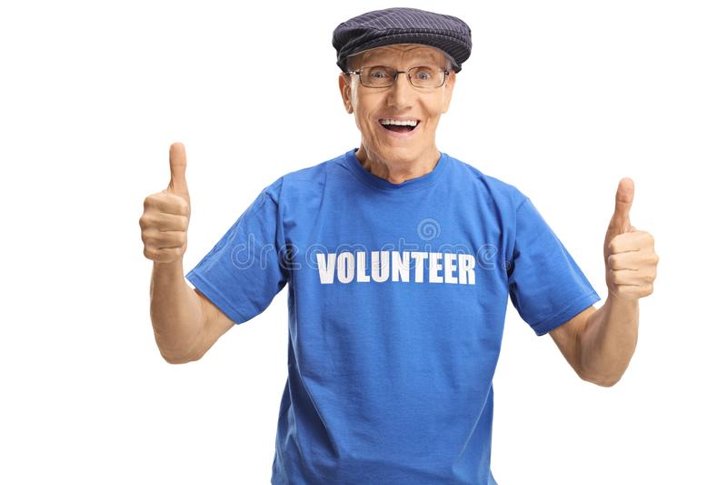Voluntário masculino idoso alegre em um t-shirt azul que mostra os polegares acima fotos de stock