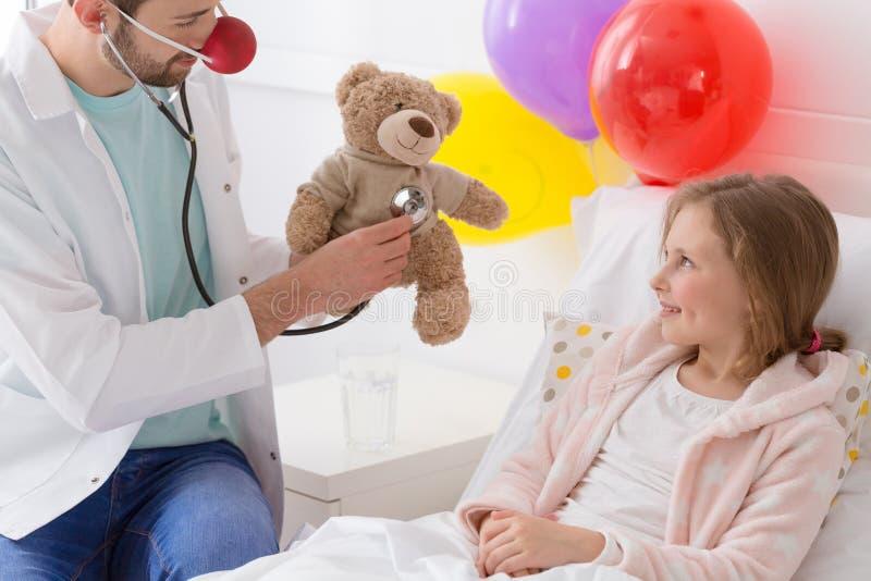 Voluntário novo que joga com uma criança doente fotos de stock royalty free