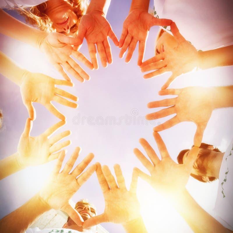 Voluntários com mãos junto contra o céu azul fotografia de stock