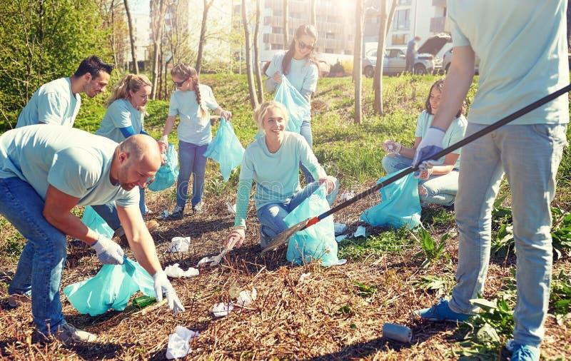 Voluntários com os sacos de lixo que limpam a área do parque fotografia de stock royalty free