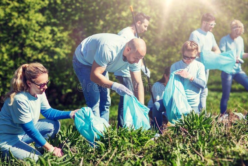 Voluntários com os sacos de lixo que limpam a área do parque imagem de stock