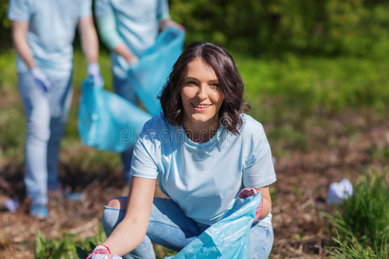 Voluntários com os sacos de lixo que limpam a área do parque foto de stock