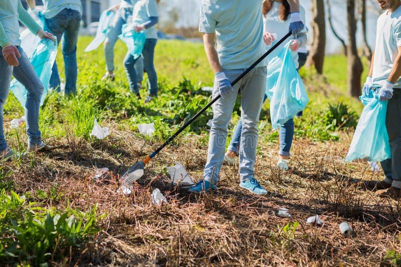Voluntários com os sacos de lixo que limpam a área do parque fotos de stock