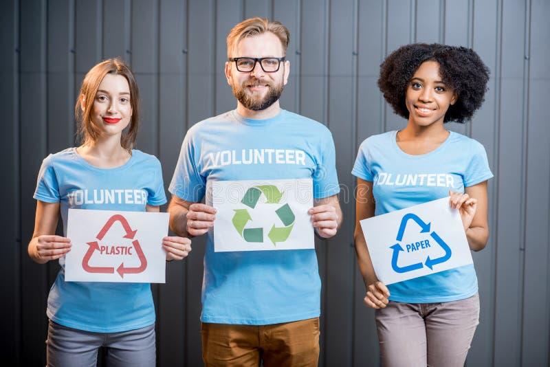 Voluntários com sinais de classificar o desperdício imagens de stock royalty free