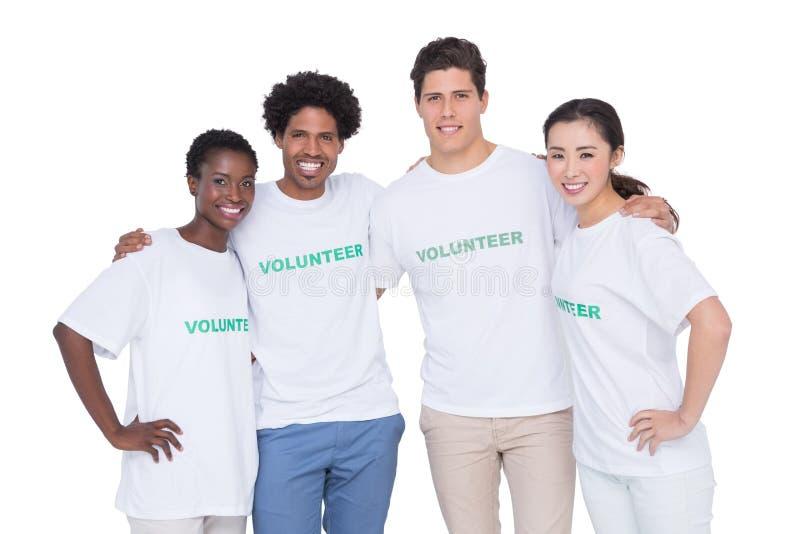Voluntários de sorriso novos que olham a câmera fotografia de stock royalty free
