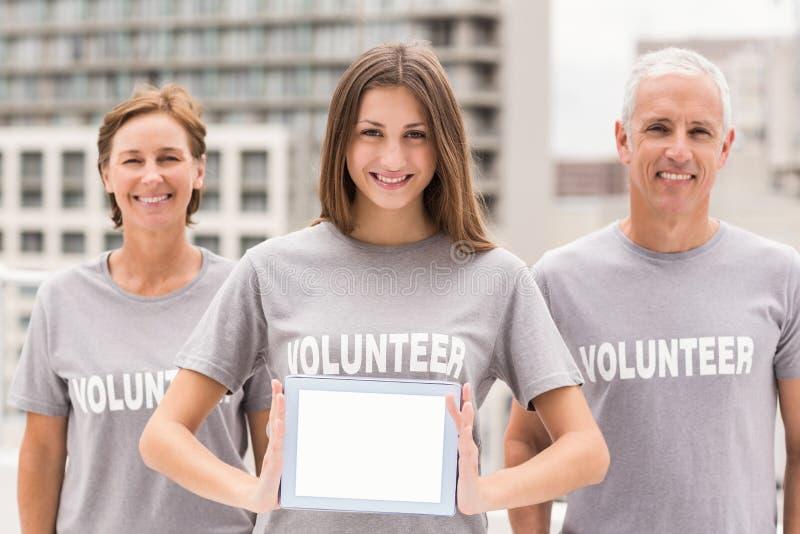 Voluntários de sorriso que mostram a tabuleta vazia imagem de stock