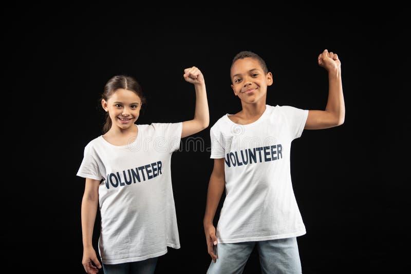 Voluntários deleitados dos jovens que vestem as camisas brancas fotografia de stock