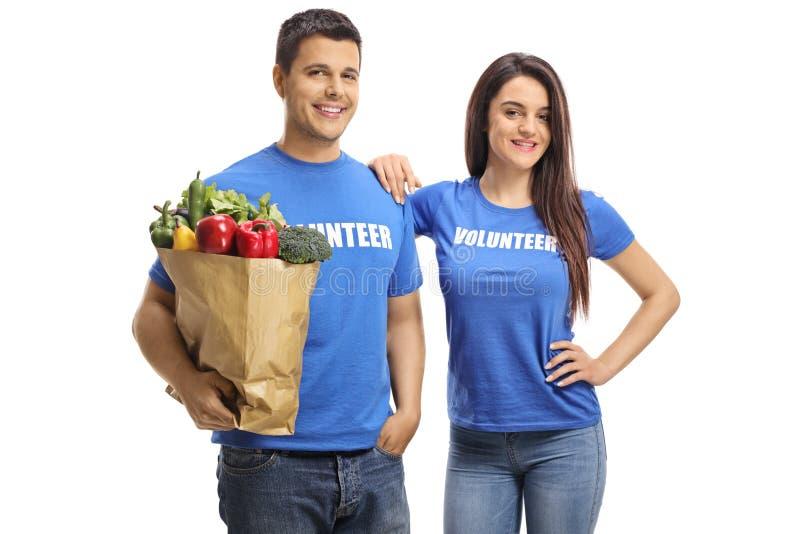 Voluntários do homem novo e da mulher que guardam um saco dos vegetais e dos frutos imagens de stock